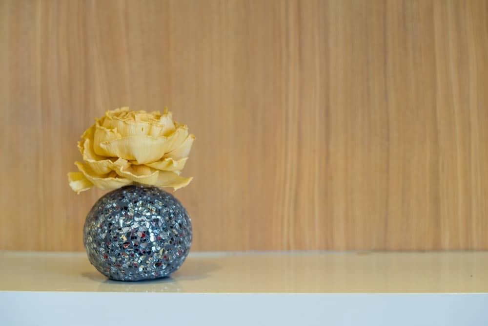 Một thiết lập trang trí của một bông hồng giấy vàng trong một chiếc bình lấp lánh.