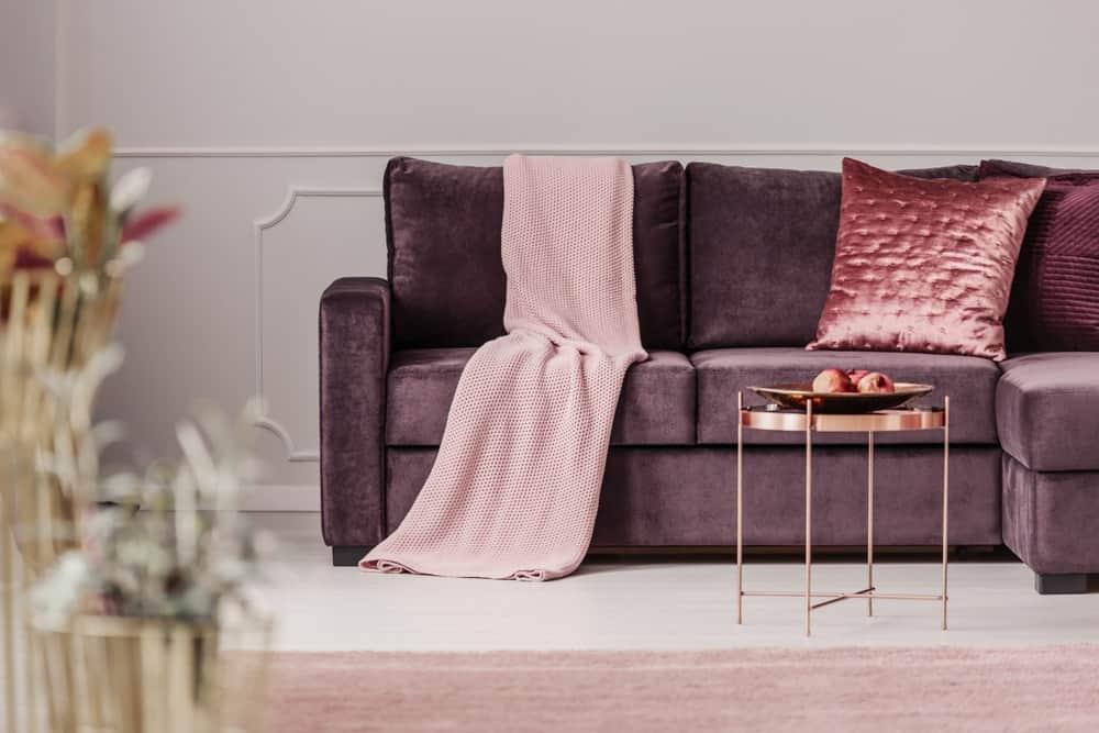 Cận cảnh phòng khách có một chiếc ghế dài bằng nhung màu tím trên bức tường trắng.