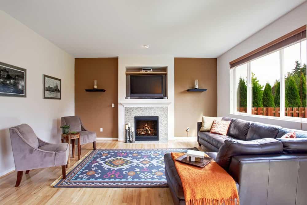 Một phòng khách sáng sủa đơn giản được bổ sung bởi tấm thảm có hoa văn nhiều màu sắc.