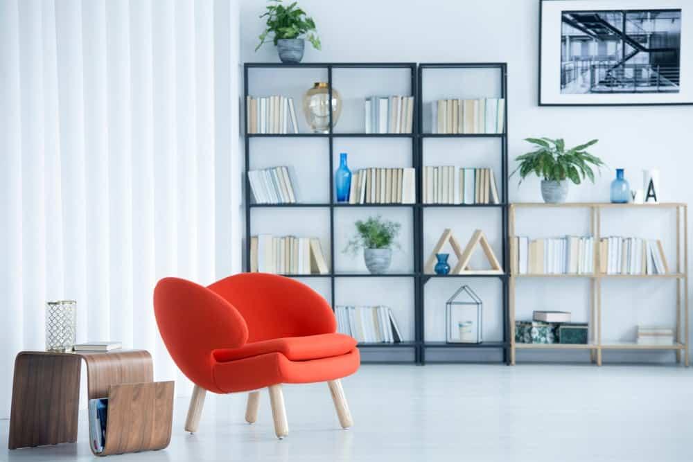 Một phòng khách kiểu công nghiệp đơn giản được bổ sung bởi giá sách dựa vào bức tường trắng.
