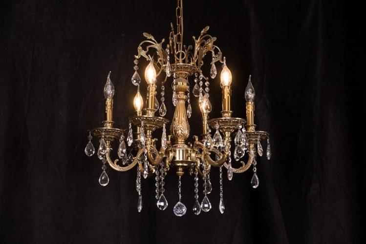 Cận cảnh một chiếc đèn chùm hùng vĩ với pha lê và ánh sáng vàng.