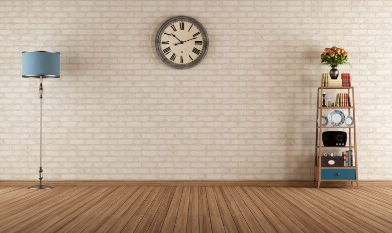 Một bức tường gạch trắng được bổ sung bởi đèn đứng và kệ gỗ.