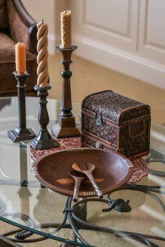 Một bàn cà phê thủy tinh được trang trí với chân nến, một cái rương gỗ và một cái đĩa gỗ.