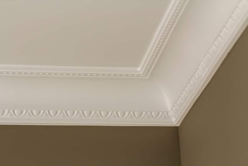 Cận cảnh khuôn đúc vương miện ở giữa những bức tường màu xám và trần nhà màu trắng.