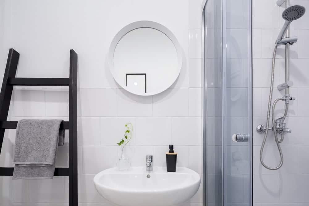 Một phòng tắm đơn giản được bổ sung bởi thang gỗ tối màu làm giá treo khăn.