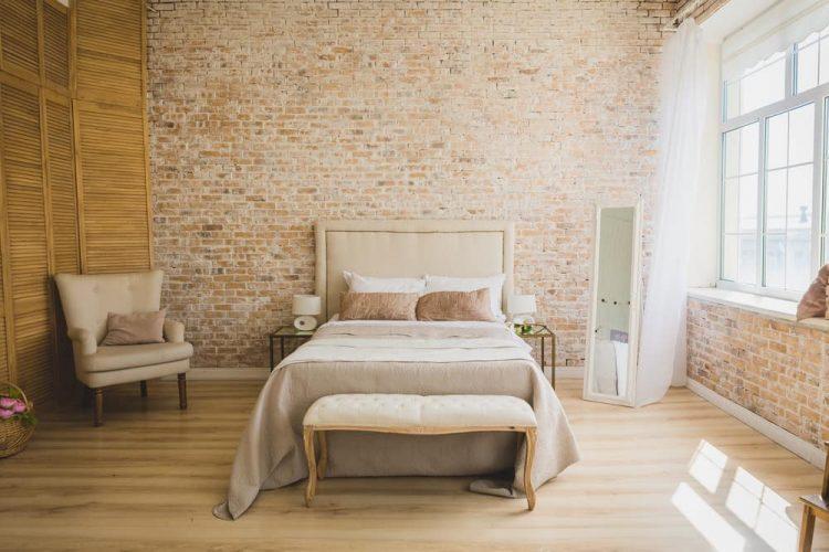 Một phòng ngủ chính đáng yêu với những bức tường gạch và ánh sáng tự nhiên rộng rãi.