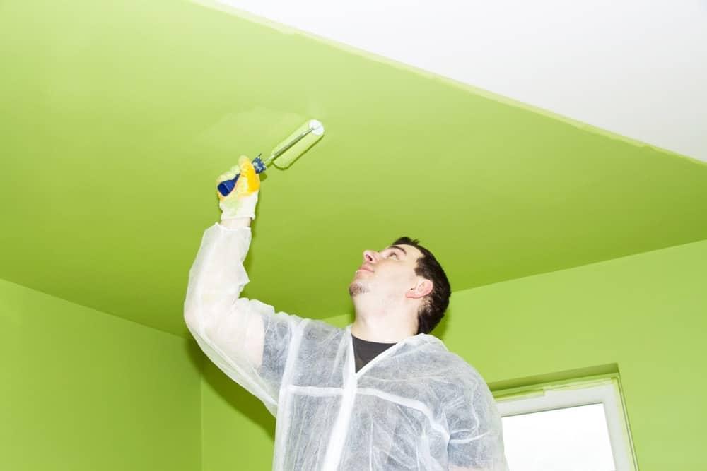 Một người đàn ông sơn trần nhà bằng sơn xanh bơ bằng con lăn.
