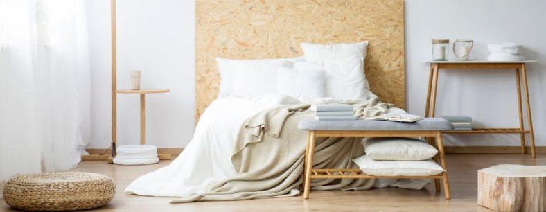 Một phòng ngủ ấm cúng với một chiếc ghế gỗ dưới chân giường phù hợp với bàn điều khiển.