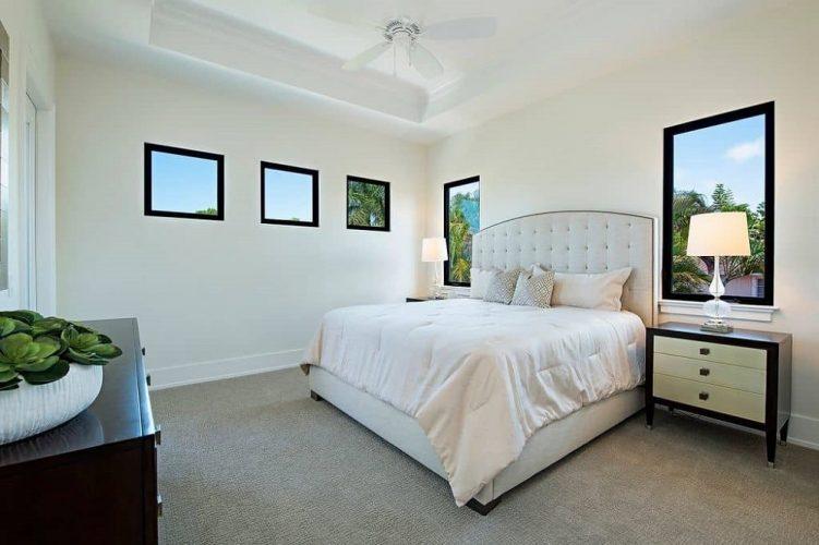 Các yếu tố màu trắng sáng của phòng ngủ này như tường, trần khay và giường lớn với đầu giường búi lớn tất cả đều khớp với nhau.  Những thứ này làm cho các yếu tố màu đen như khung cửa sổ và ngăn kéo đầu giường nổi bật.