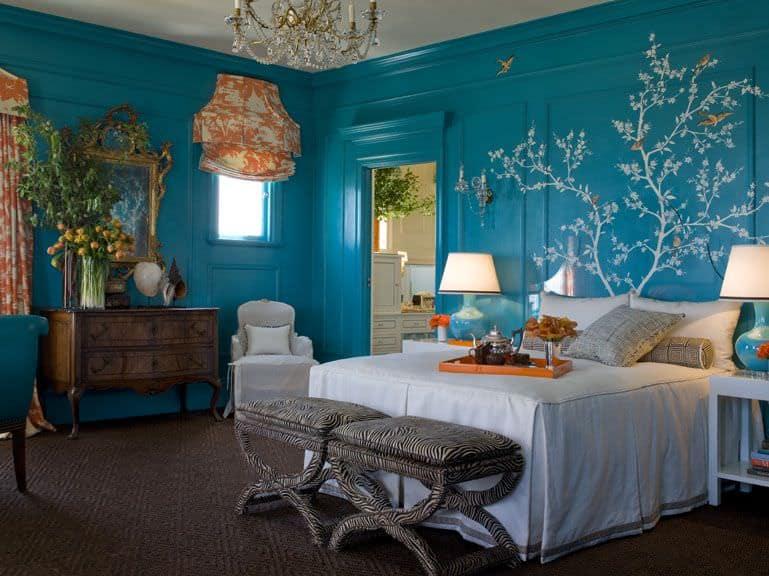 Phòng ngủ phong cách nội thất chiết trung màu xanh chiết trung với tranh tường, màn cửa màu cam và thảm trải sàn.