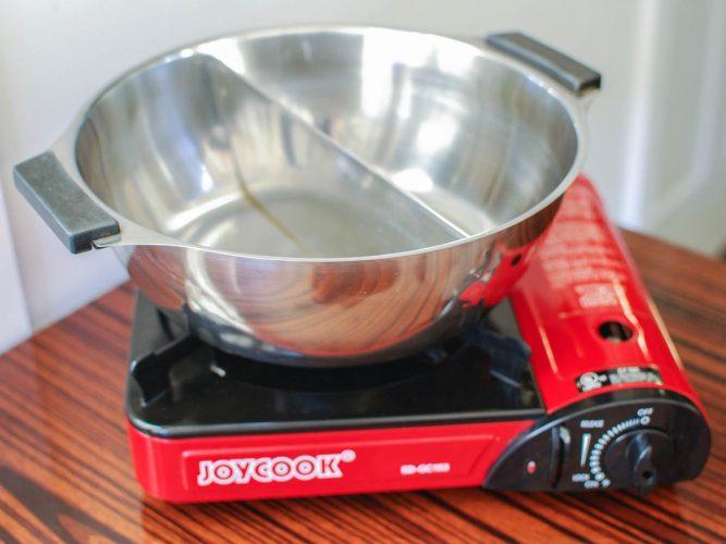 Nồi lẩu có Bộ chia trên bếp đốt butan di động để nấu lẩu Trung Quốc.