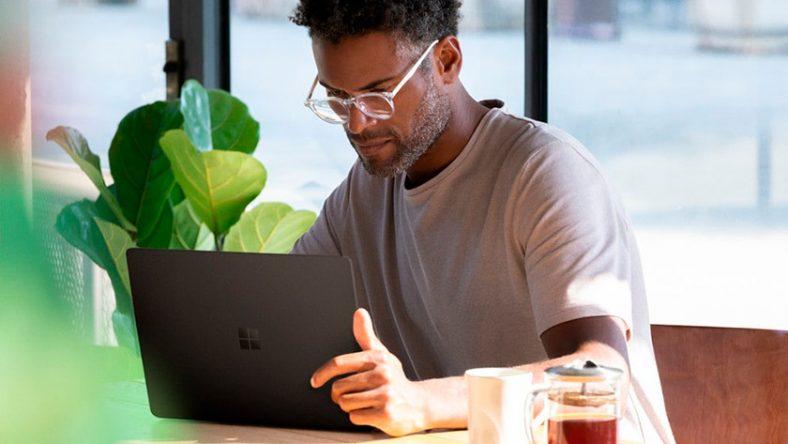 Người đàn ông đang làm việc trên một Laptop 13 inch trong quán cà phê với cây trồng ở phía sau.