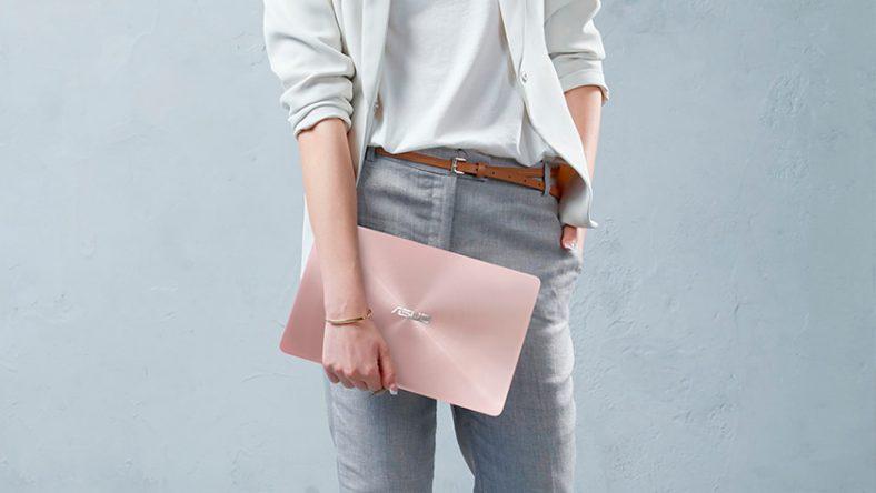 Người phụ nữ cầm Laptop 14 inch bằng một tay, tay còn lại ở hông.